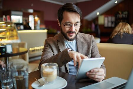work addicted: Businessman with touchpad networking in cafe