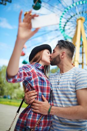 amorous woman: Kissing dates making selfie outdoors