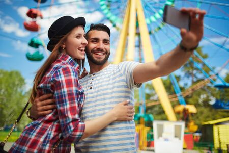 amorous woman: Cheerful dates making selfie in amusement park
