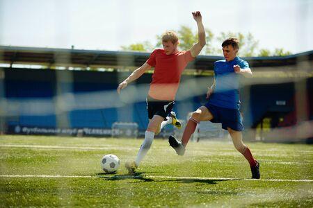 Dos deportistas jóvenes jugando al fútbol