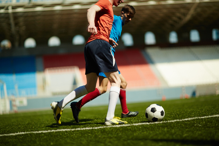 opposing: Two opposing footballers following soccer ball Stock Photo