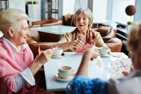 grupos de personas: Mayores con tarjetas de pasar el tiempo libre en el café Foto de archivo