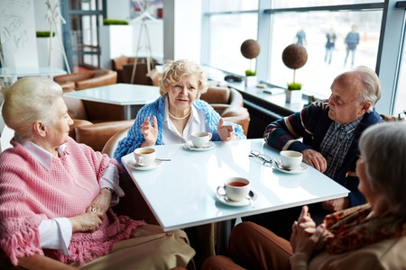 Seniors talking by cup of tea in cafe