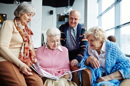 les personnes âgées en regardant à travers les magazines de loisirs
