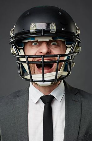 executive helmet: Shouting buasinessman in football helmet and grey formalwear with tie perhaps playing football and expressing his emotions in such a way, perhaps he sees his rival going to win Stock Photo