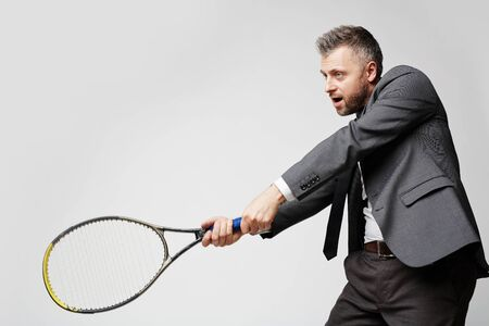 business rival: Confident employer in smart suit artfully playing tennis with his business rival, the idea of image is professionalism of modern entrepreneur
