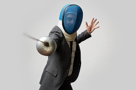 business rival: Businessman in fencing mask and formal suit attacking his rival with foil to defense himself and his business or company in economically hard period Stock Photo