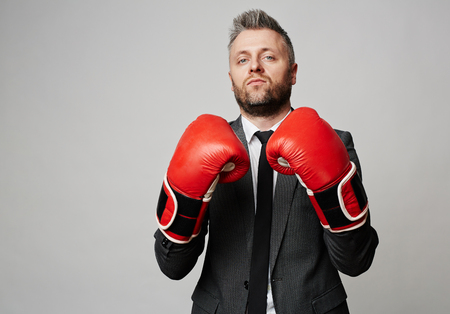 Powerful employer or business leader in boxing gloves looking at camera with confident expression, he ir ready to face difficulties in starting new business and able to do all his best to be a success