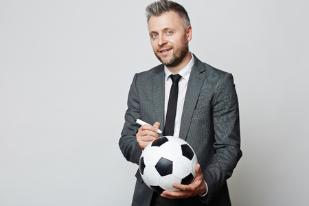autograph: Experienced businessman with soccer ball writing his autograph on it - perhaps he is famous football or business coach, he looks like real champion and professional in business training