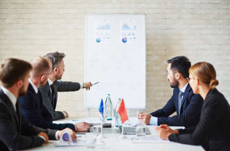briefing: Successful leader explaining data to colleagues at briefing Stock Photo