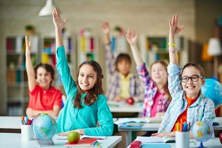 Okos lányok és fiúk a kezek felemelésével a választ, Stock fotó
