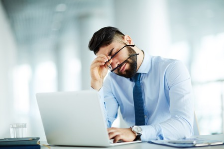 tired businessman: Businessman at his workplace tired of work Stock Photo