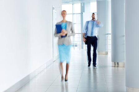 blurred people: Blurred image of business people walking along the office corridor