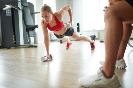 tricep: Young woman exercising with dumbbells on the floor