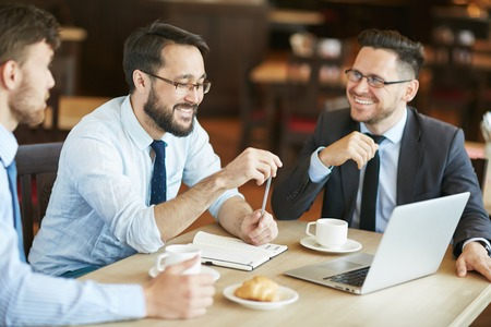 discussing: Colleagues discussing data in cafe Stock Photo