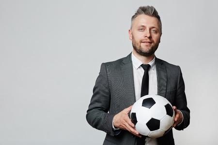 ボールを持つエレガントなビジネスマンやサッカー コーチ