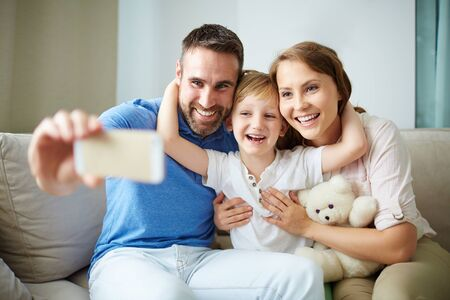 affectionate: Affectionate family making selfie on cellphone