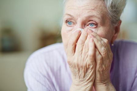 persona triste: Triste mujer mayor secándose las lágrimas