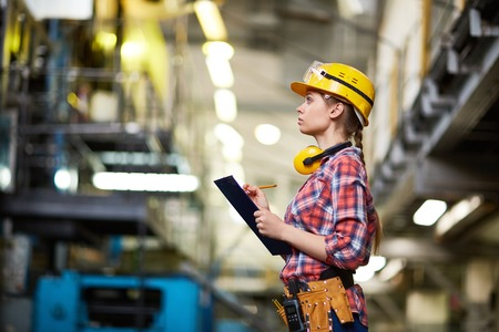 executive helmet: Female mechanic making notes at work in plant