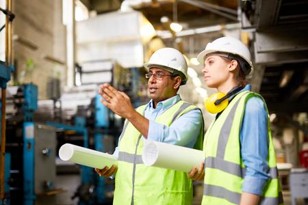 executive helmet: Engineer in helmets workng in group at factory
