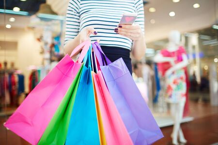 consumer: Consumer with bags writing sms after shopping Stock Photo