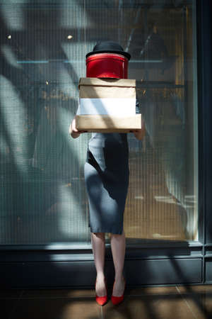 shopper: Shopper with stack of boxes standing by trade center Stock Photo