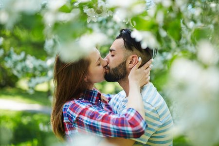 adult valentine: Young couple kissing in blooming garden