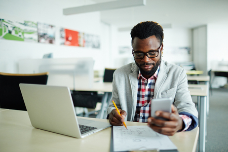 work addicted: Young businessman analyzing data in office Stock Photo