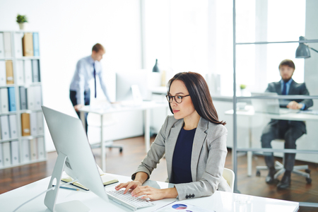 Pretty businesswoman sitting at her desk and typing on computer Stockfoto