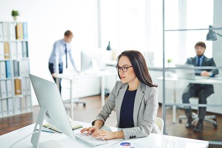 Pretty zakenvrouw vergadering op haar bureau en het typen op de computer Stockfoto