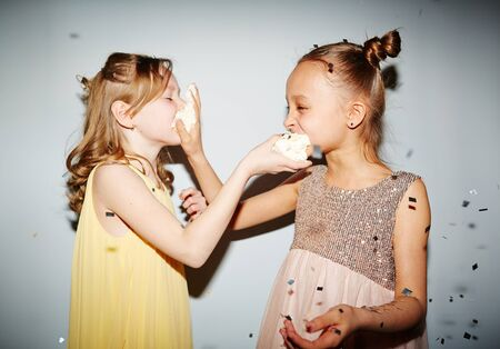 party pastries: Two little girls giving a piece of cake to each other Stock Photo