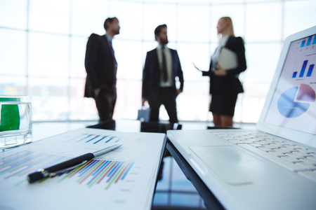economic: Close-up of business plan with people working in the background