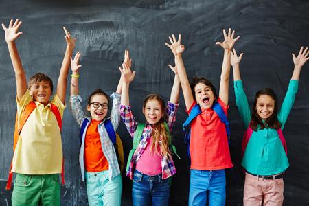 escolares excitados de pie con las manos en alto