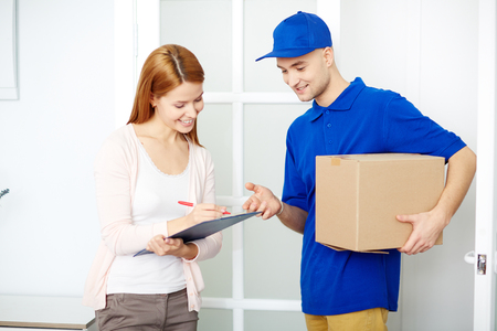 Postman with parcel showing young woman where to sign Archivio Fotografico