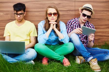 ragazza Bored seduto tra due ragazzi con i gadget