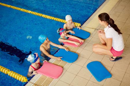 niños nadando: Los niños con swimboards escuchar a su entrenador