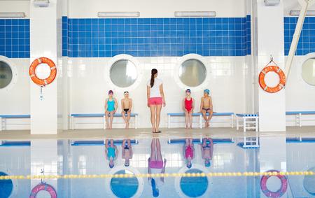 escucha activa: Los ni�os activos que escuchan el entrenador en la piscina