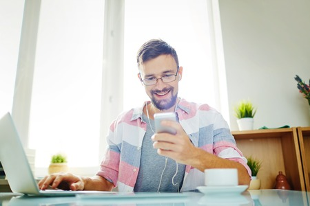 work addicted: Young office worker with earphones and smartphone Stock Photo