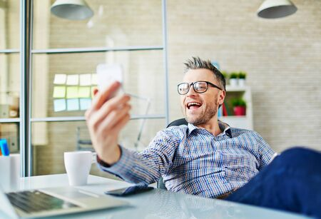 work addicted: Businessman making selfie at workplace
