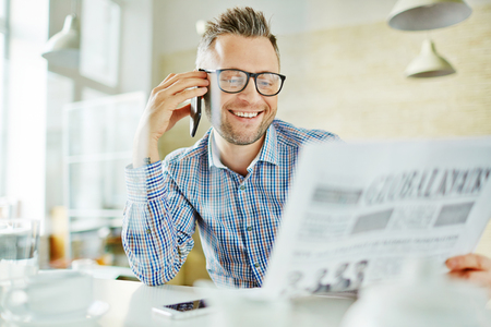 work addicted: Businessman talking by cellphone while reading newspaper