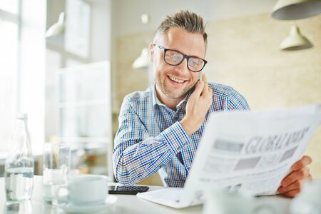 work addicted: Happy employee with newspaper calling in office