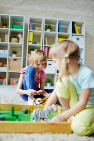 youthful: Youthful girls playing with toys in kindergarten