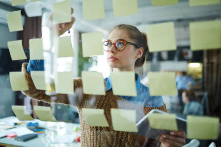 reminders: Young businesswoman reading reminders in office Stock Photo