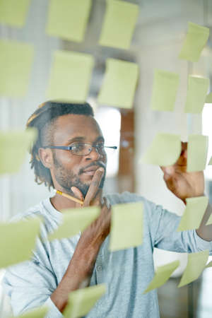 reminders: Employee reading reminders on notepapers Stock Photo