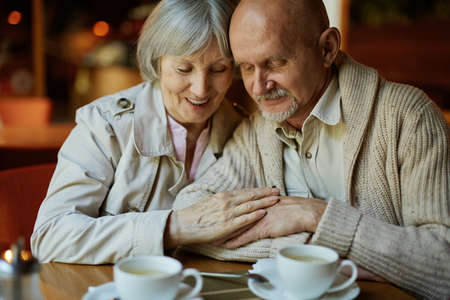 amorous woman: Affectionate senior couple relaxing in cafe