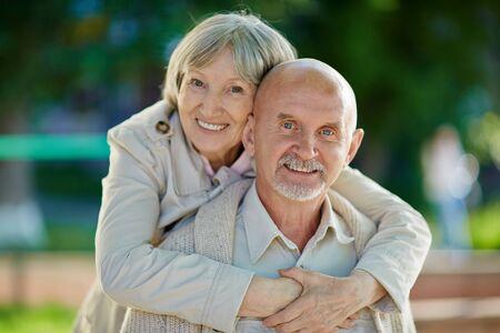 couples hug: Happy senior female embracing her husband outdoors