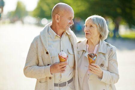 amorous: Amorous seniors with ice-cream taking walk