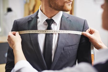 ビジネスマンのジャケットの測定前を調整します。