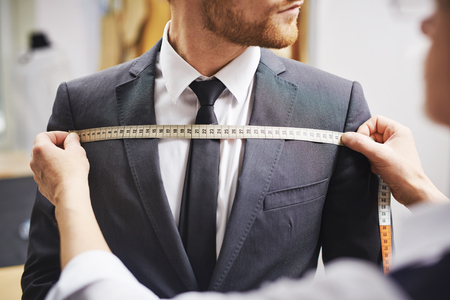 Tailor measuring front of businessman jacket