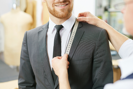 Tailor hands with tape measuring jacket collar